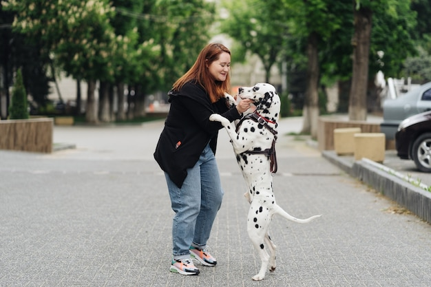 View of young caucasian woman playing and training her dalmatian dog