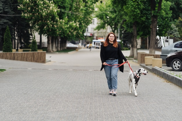 View of young caucasian woman walking at city during morning time with dalmatian dog