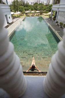 Above view of young woman enjoying hotel pool