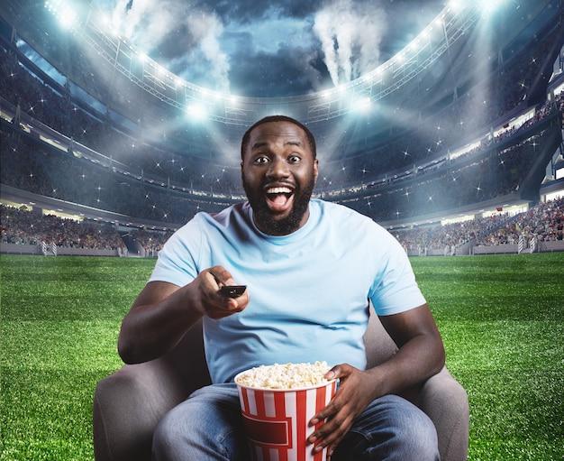視聴者は彼の肘掛け椅子に座っているスタジアムの真ん中に位置しています