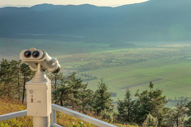 谷を見下ろすslivnica山の展望台で望遠鏡を見る