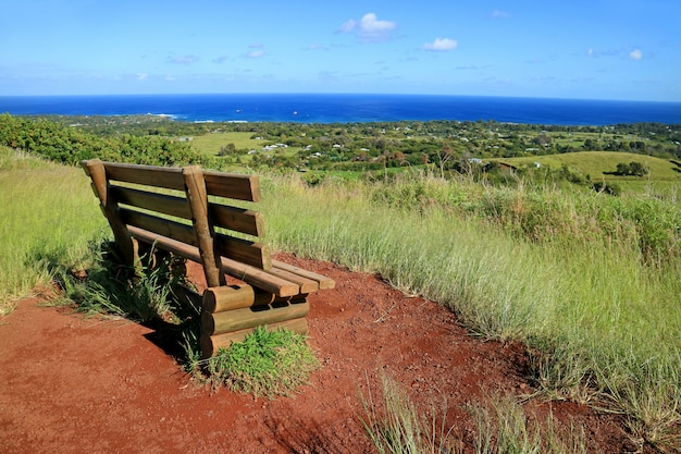 Viewpoint for hanga roa and pacific ocean with a wooden bench on red scoria at puna pau volcano