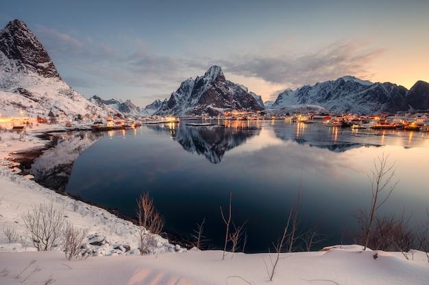 日の出の朝の冬の漁村と山脈の視点。ノルウェー、ロフォーテン諸島