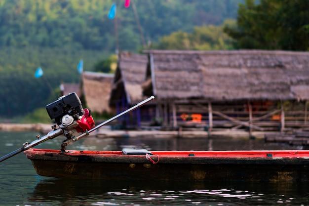 写真の真ん中にボートが浮かんでいる川や山々の景色、そして背景にはたくさんの浮かぶいかだがあります。
