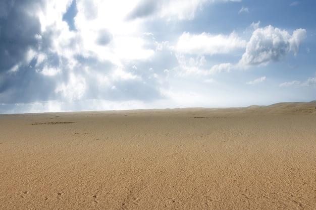 Вид на песчаные дюны на фоне голубого неба