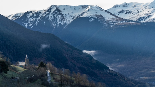Взгляды церков городка mont в vielha с снежными горами на заднем плане.