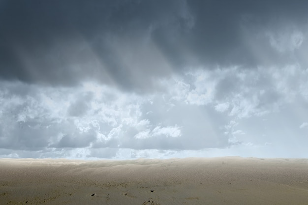 Views of sand dune with a dramatic sky