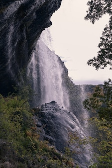 Views of a waterfall with water falling on a large rock in the foreground