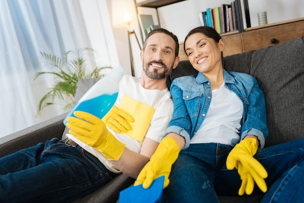 Vigorous positive sincere couple lying on the sofa while smiling and holding cleaning means