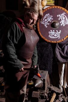 バイキングの鍛冶屋は古いビンテージフォージで武器を偽造します。