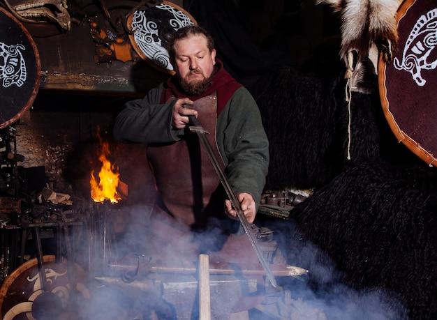 バイキングは鍛冶屋で武器と剣を鍛造します。戦士の服を着た男が鍛冶場にいます。