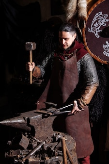Viking forges weapons and swords in the smithy. a man in a warrior's clothes is in the smithy