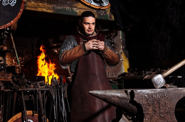 Viking forges weapons and swords in the smithy. a man in a warrior's clothes is in the smithy. Free Photo