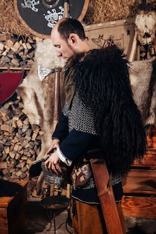 Викинг позирует на фоне древнего интерьера викингов.
