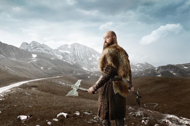Викинг с топорами в руках у скалистых гор