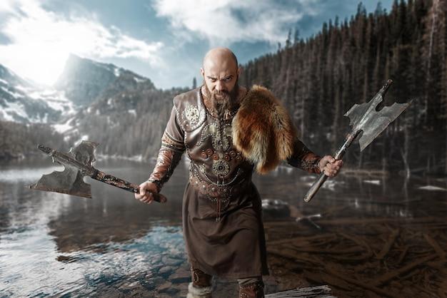 Викинг с топорами в руках, одетый в традиционную нордическую одежду, стоит у озера. древний воин у реки, скалистые горы