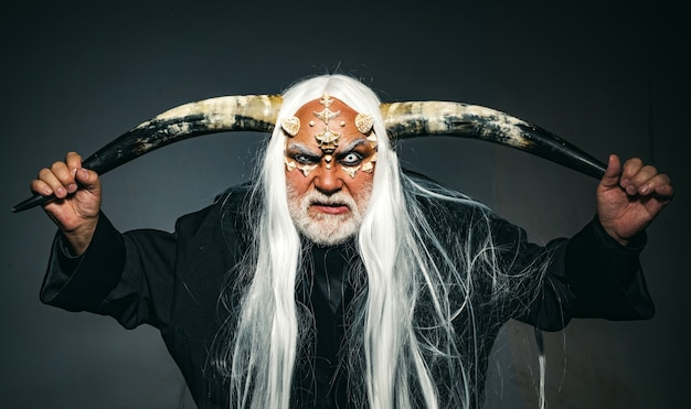 Viking with a horned head man wizard with fantastic make up on demon face man evil with horns dracul...