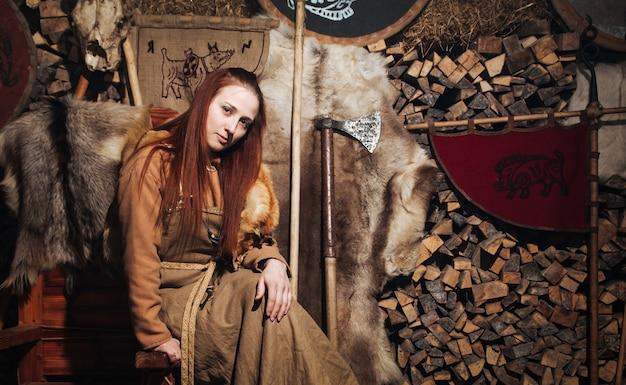 Женщина-викинг позирует на фоне древнего интерьера викингов.