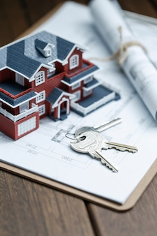 Модель виллы, ключ и рисунок на ретро-столе (концепция продажи недвижимости)
