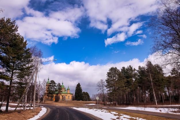 Деревня католическая церковь по дороге в зимнее солнце. большой вид изображения пейзаж с церковью на возвышенности, голубое небо с облаками, изумительный вид. предпосылка сезонной зимы финляндии. копировать пространство