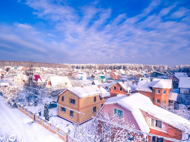 Village in forest winter aerial view blue cloudy sky
