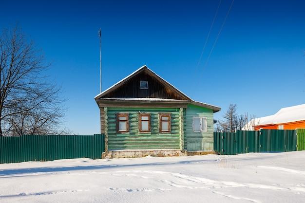 추운 겨울 날에 얼어 붙은 창문이있는 마을 집