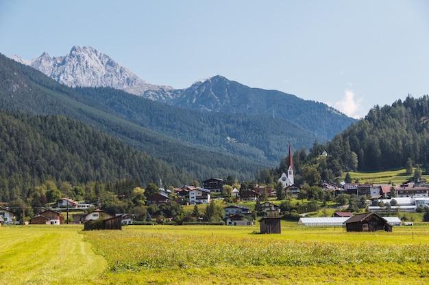 Деревня на горном лугу. зеленый луг и горы