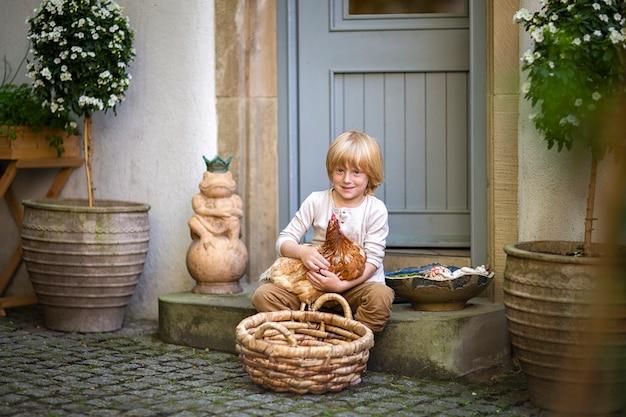 村の生活。玄関近くの階段の庭に茶色のチキンと大きなバスケットを持つ田舎の少年