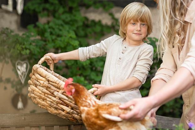 村の生活。茶色の鶏と庭に大きなバスケットを持つ田舎の少年