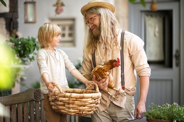 村の生活。玄関近くの庭にあるパディブラウンチキンと大きなバスケットを持つカントリーボーイ