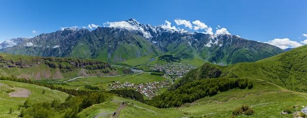 봄에 kazbegi 지구 조지아 파노라마 풍경에서 산 배경에 마을