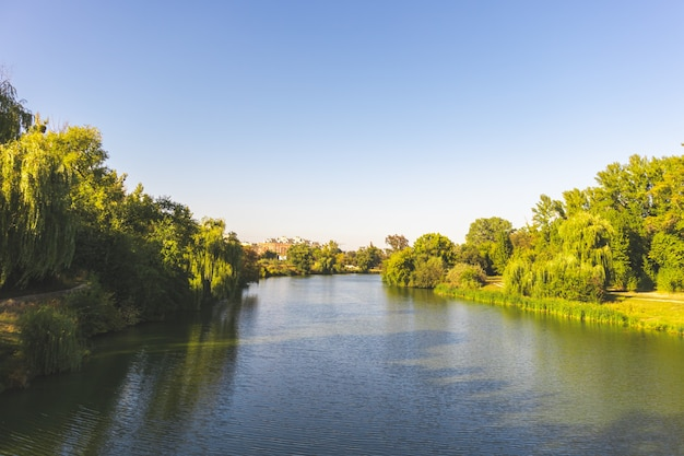 Village river at sunset, clear blue sky above photo