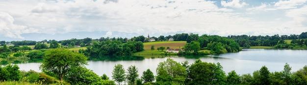 村の小さな教会の湖とフランスのピレネー山脈の背景