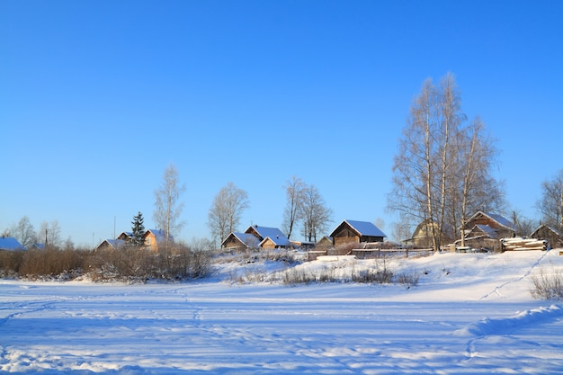 Village in snow on coast river