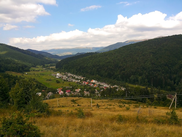 Village in the valley against the backdrop of several wooded mountains and blue sky with clouds