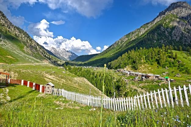 Вид на деревню и травянистые холмы