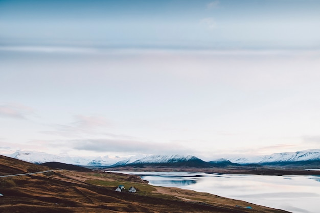 Village with farms in a rural area of the mountains of iceland, with snowy mountains in the background.