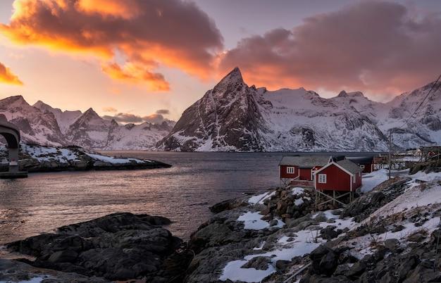 ノルウェーのロフォーテン諸島の日没で雪に覆われた背景の山々と海沿いの赤い小屋の村
