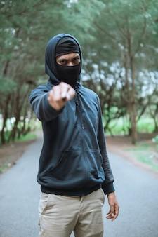 Злодей в маске с ножом в черной толстовке с капюшоном указал на нож, стоя на дороге