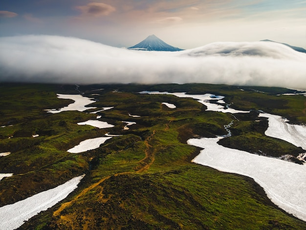 Vilyuchinsky volcano with clouds at sunrise. kamchatka peninsula, russia. aerial drone view. beautiful summer landscape