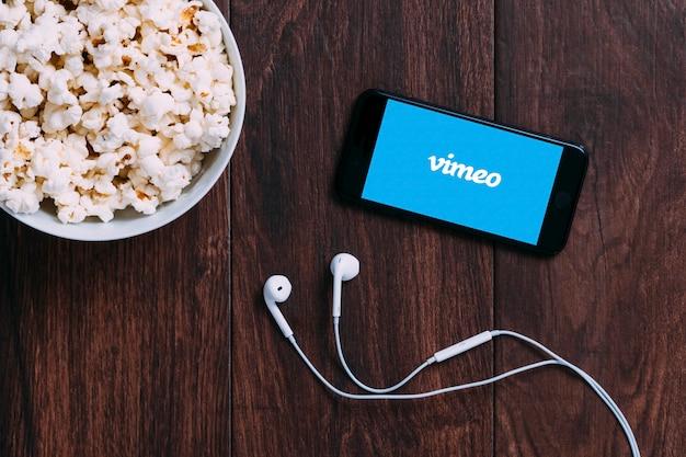 Стол с бутылкой попкорна и логотипом vimeo на apple iphone и наушниках.