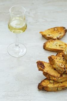 木材の背景に甘いワインvin santoとビスコッティクッキー。甘いワインとデザートのビスコッティのグラス。