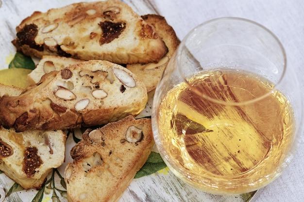 Печенье бискотти с сладким вином vin santo на деревянный стол.