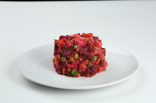 흰색 배경에 고립 된 하얀 접시에 vinaigrette 샐러드. 삶은 야채를 곁들인 전통 러시아 비트 뿌리 샐러드