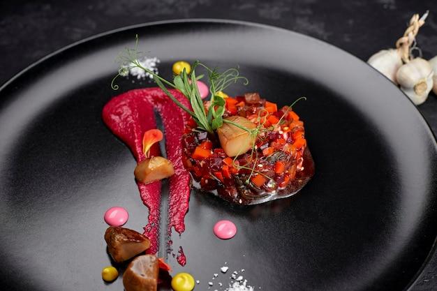 Салат винегрет на черном фоне, на черной тарелке с чесноком
