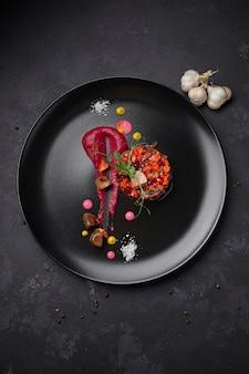 黒の背景に、ニンニクと黒のプレートにビネグレットサラダ