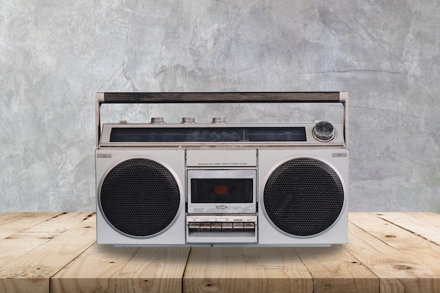 Vinatge stereo on wooden table and concrete  wall texture and background.