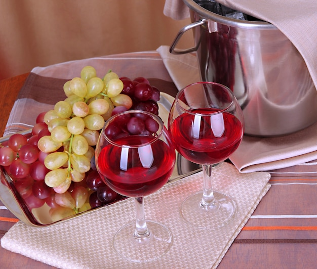 Vine and glasses on round table on tablecloth