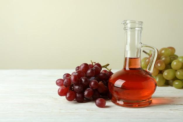白い木製のテーブルに酢とブドウ