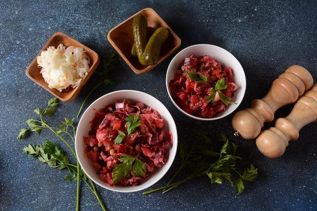 식초 또는 식초. 회색 배경에 흰색 그릇에 요리하고 절인 야채, 완두콩, 비트 뿌리를 넣은 전통적인 러시아 레드 샐러드.